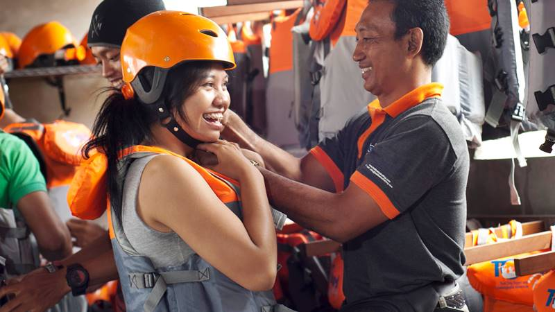 Wearing helmet and life jacket for rafting safety